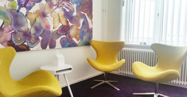 Individuele gespreksruimte geel met drie fauteuils